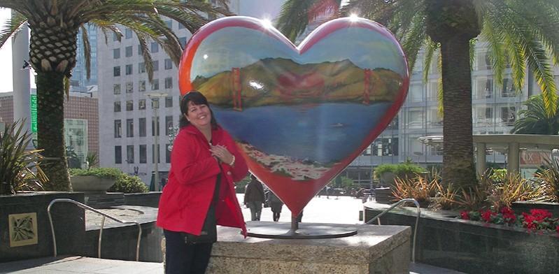 female in red coat near a big heart