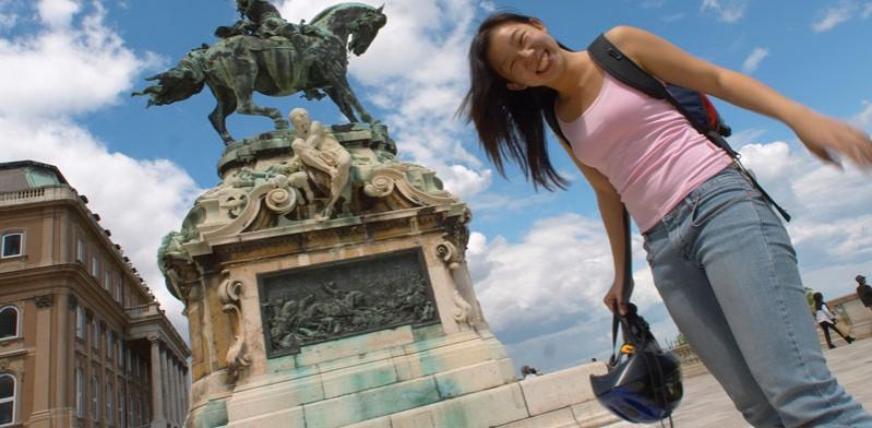girl holding helmet next to statue