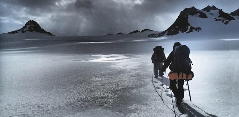 two men trekking through the snow