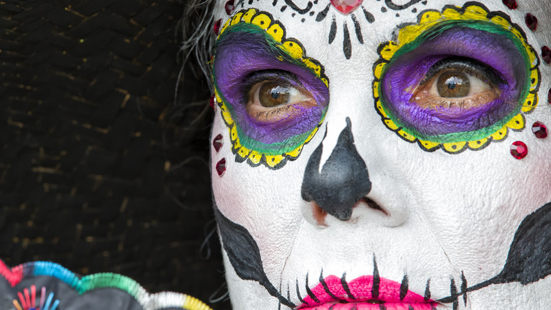 A woman in skull face-paint prepares for Day of the Dead celebrations
