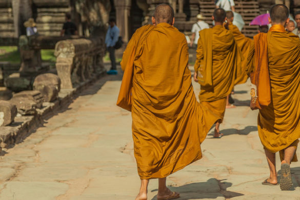 Three Cambodian monks walking along a path