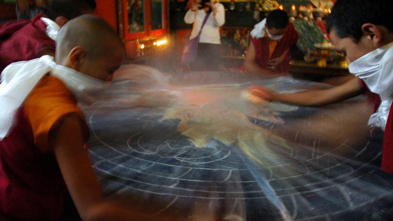 Buddhist monks clear away a mandala. Image Wonderlane, Flickr