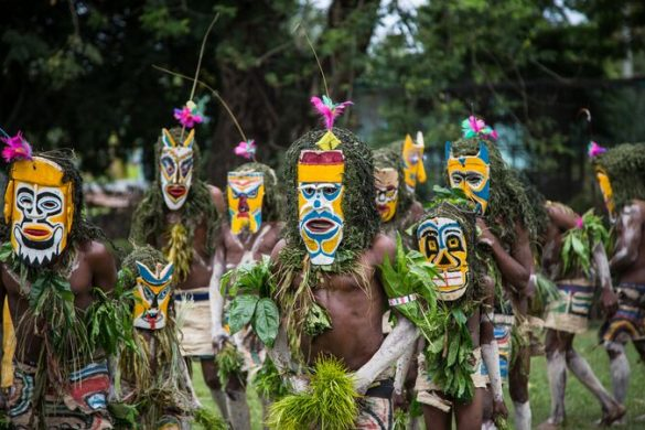 A group of men wearing traditional masks in PNG.