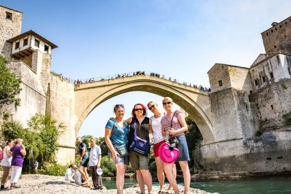 Four women standing under a beautiful old bridge in Bosnia