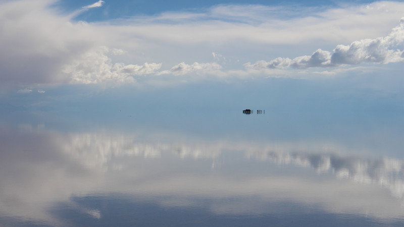 Perfect reflections of the sky with a distant 4WD