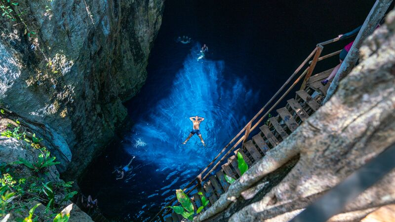 drone shot of a man swimming in the cenotes in mexico