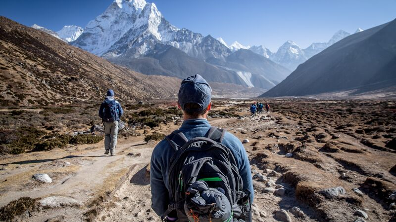 A man wearing a backpack looks at Mt Everest