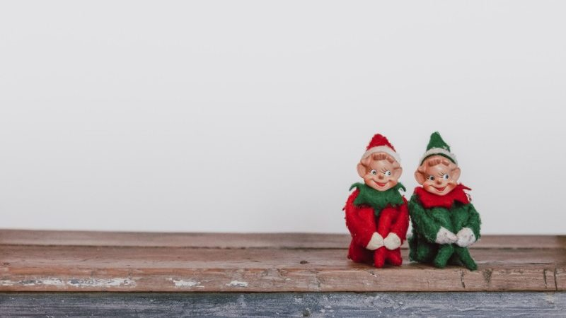 Two Christmas elf decorations sit on a shelf