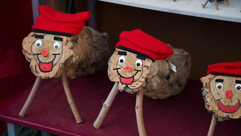 Three logs with faces wearing Christmas hats