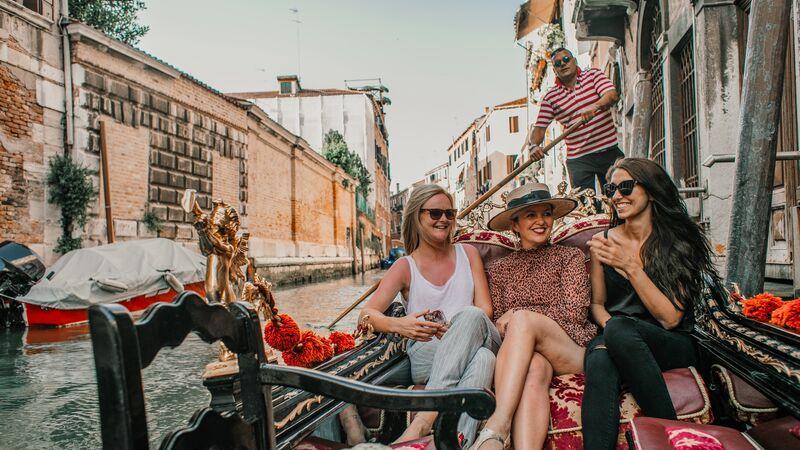 Three women on a gondola in Italy
