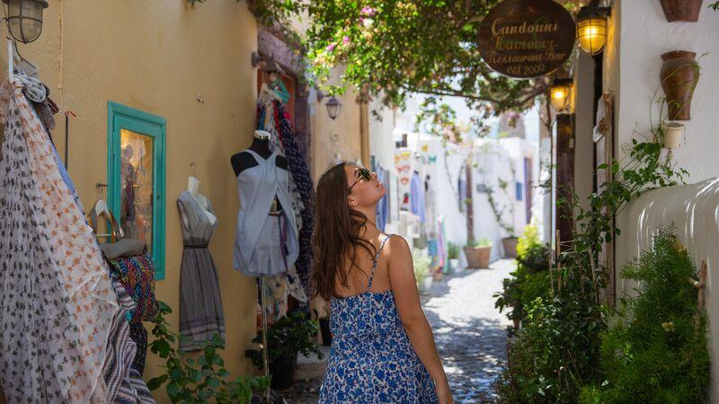 A woman walking through a village in Greece