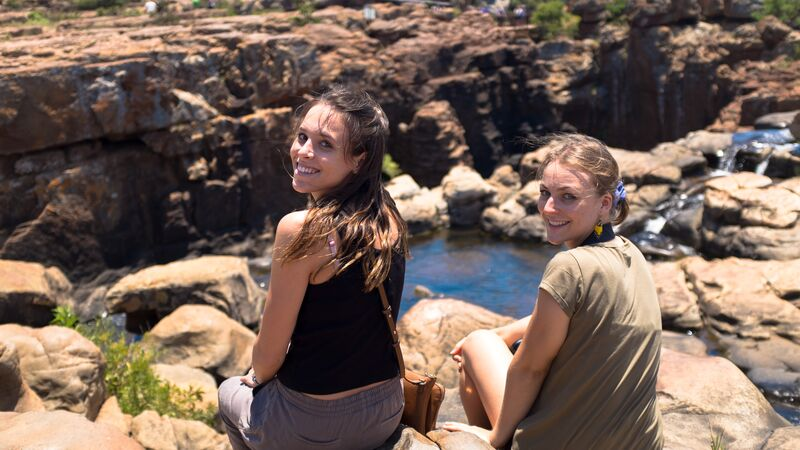 Two girls sitting at the edge of a canyon in South Africa.