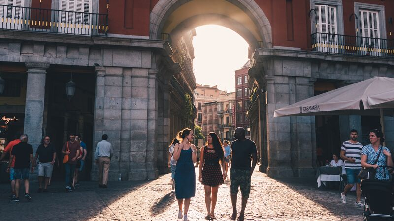 Three people walking through a square in Madrid at sunset