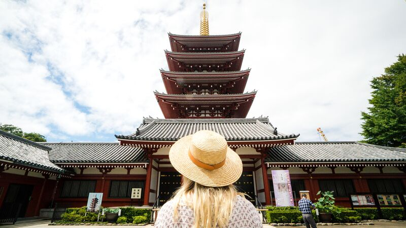 A girl wearing a straw hat in front of a temple in Japan