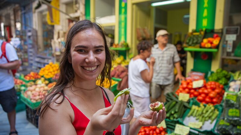 A girl eating a fig in a market