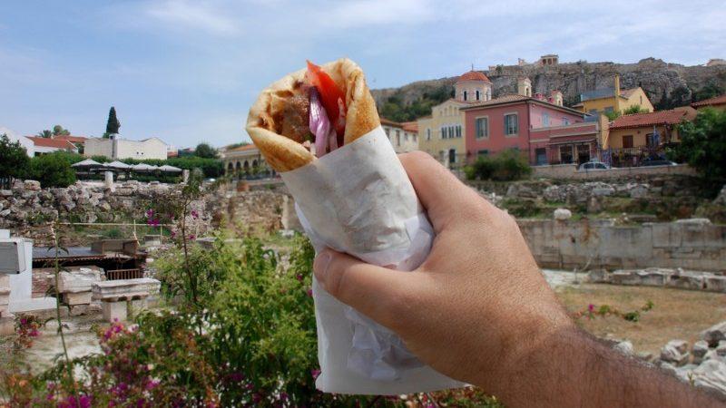 A man holds up a souvlaki in Greece