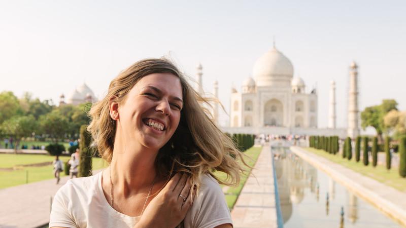 Young woman laughs outside Taj Mahal