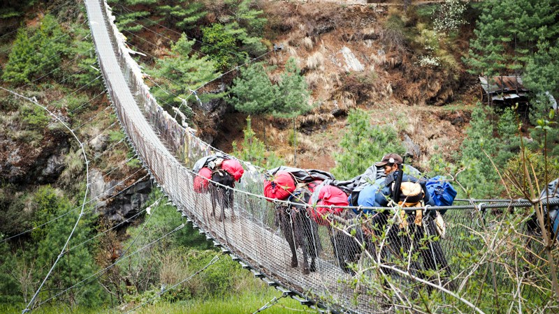 Crossing a suspension bridge in the Himalayas