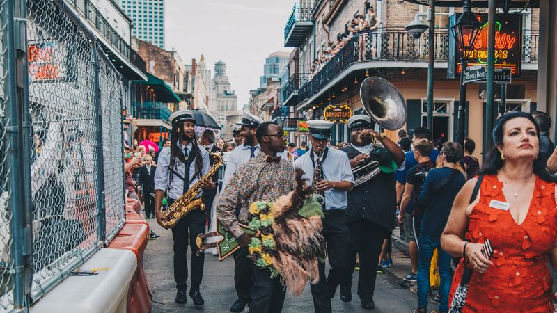 A marching band walking down a busy street in New Orleans
