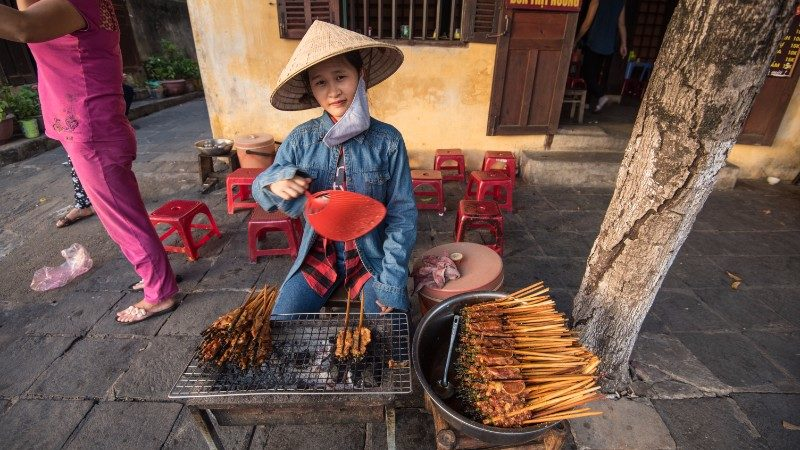 A woman sells chicken skewers by the river in Hoi An
