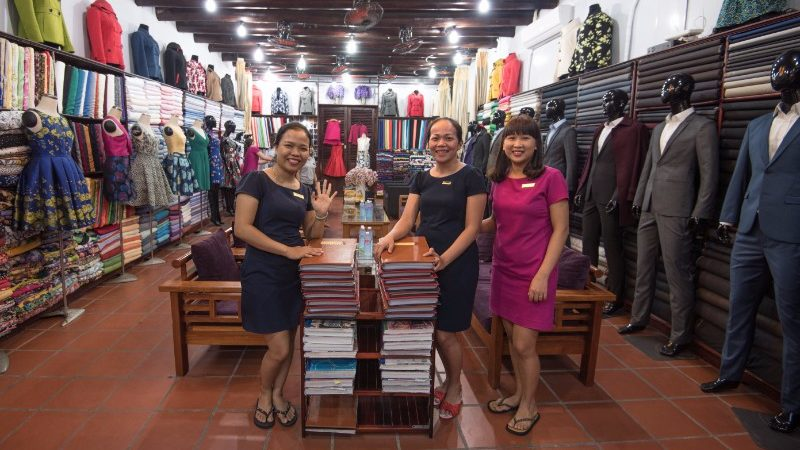 Three sales assistants in a Hoi An tailors.