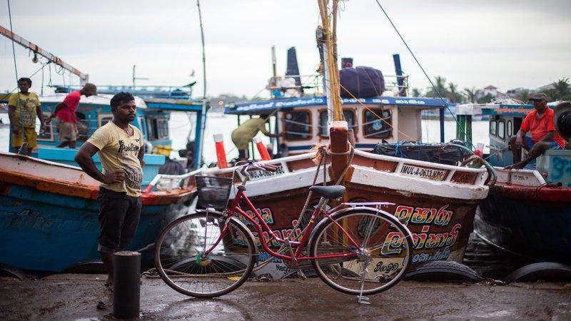 A local fisherman stands next to his bike.