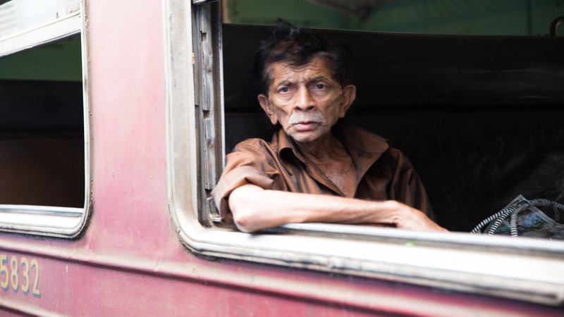 An old man stares out of the window on the train.