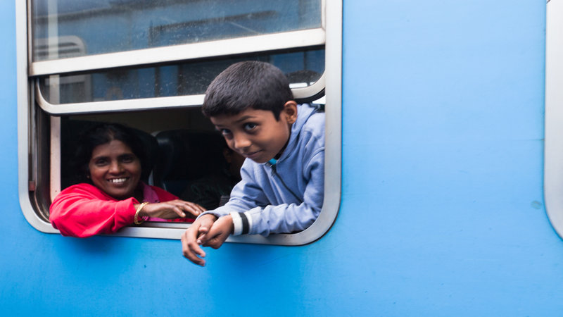 A young boy and his mother peer out of the train window.