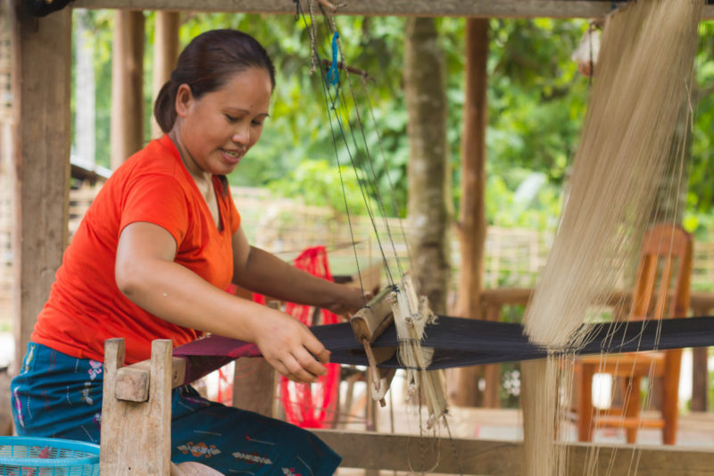 Laos Woman hand weaves textiles in Nong Khiaw