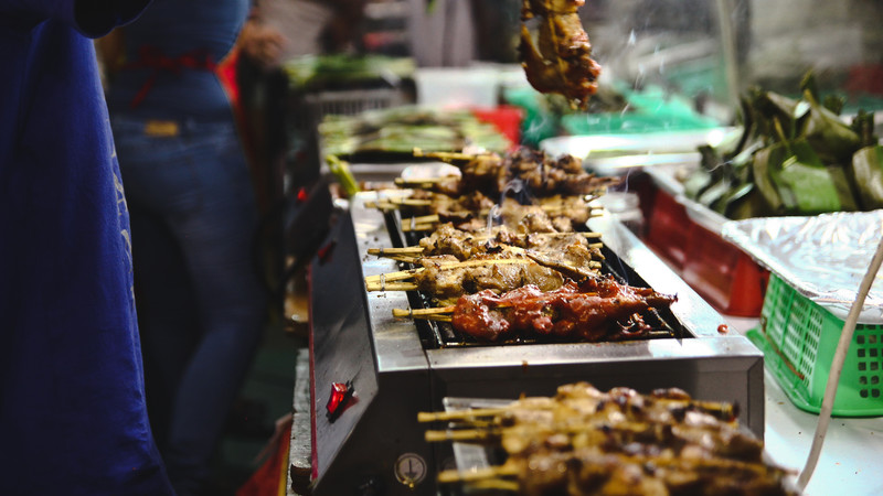 Meat skewers on the grill at the Singapore hawker markets