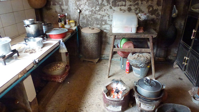 Dirt-floored kitchen, filled with pots and pans