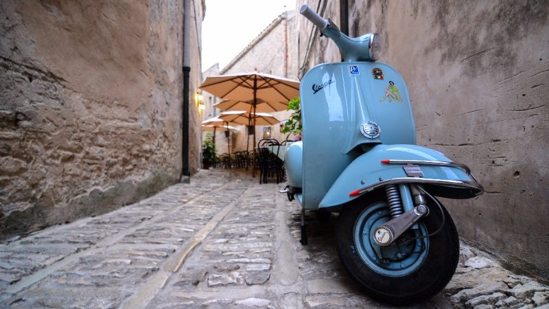 Vespa parked in cobble-stoned laneway in Italy