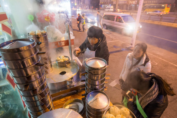 A woman dishes up fresh dumplings at a street food stall in China