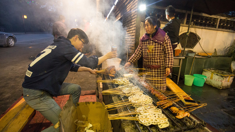 Vendors grill sizzling skewers at a street food stall in China.