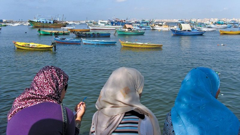 Three Egyptian women wearing headscarves look out over the water