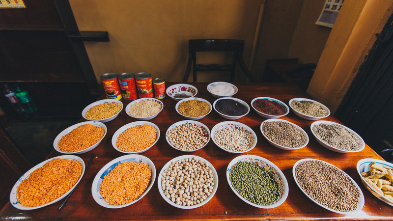 Table covered with bowls of spices, herbs and legumes in Sri Lanka