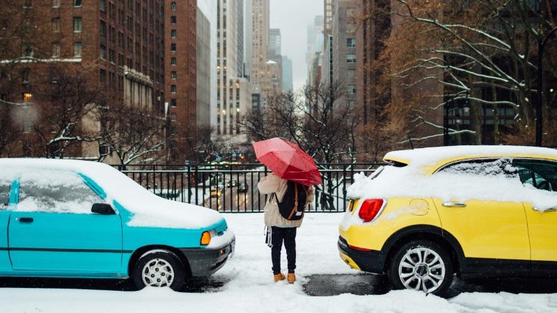 A person under a red umbrella stands between two colourful cars in the snow.