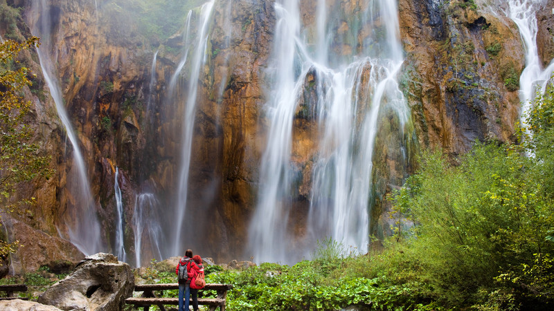 A couple stand in front of a waterfall in Plitvice Lakes