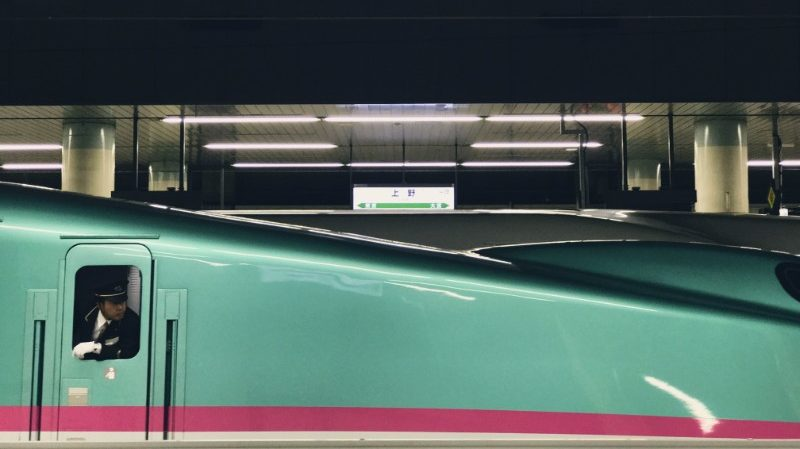 A train driver on a Japanese train leans out the window.