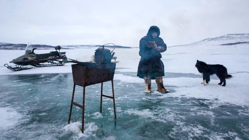 A man stands in front of his barbecue on the ice