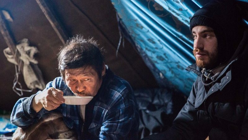 Two men share tea and soup in a chum