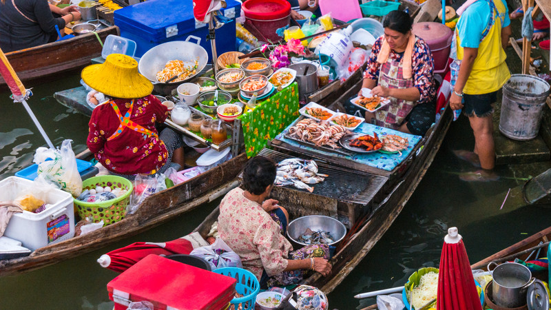 Vendors sit in longboats filled with wares at the floating markets