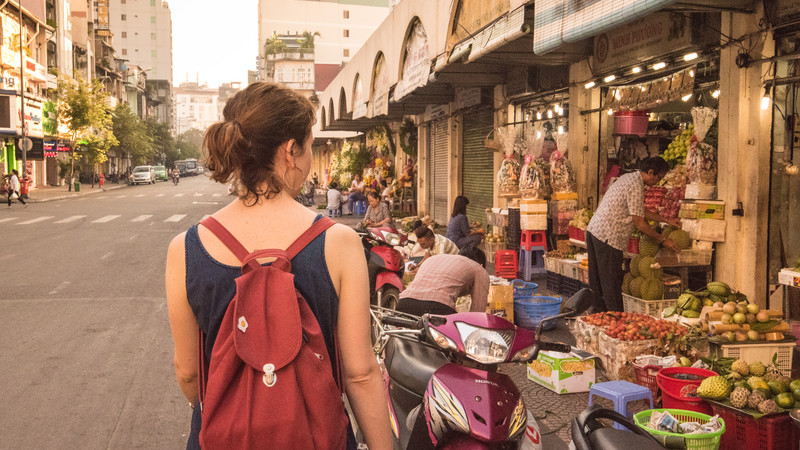 A female traveller walks down a busy street in Ho Chi Minh City