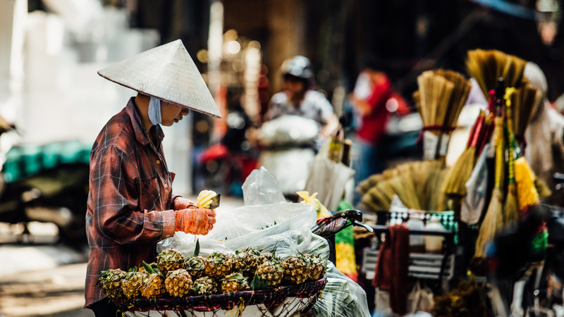 A man sells pineapples in Vietnam