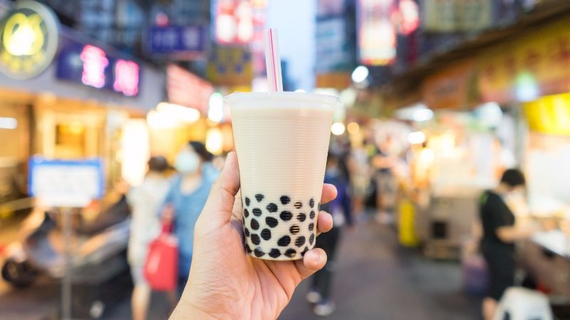 A hand holds a cup of bubble tea up to the camera in busy Taiwan