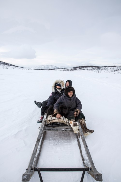Three travellers sled across the ice