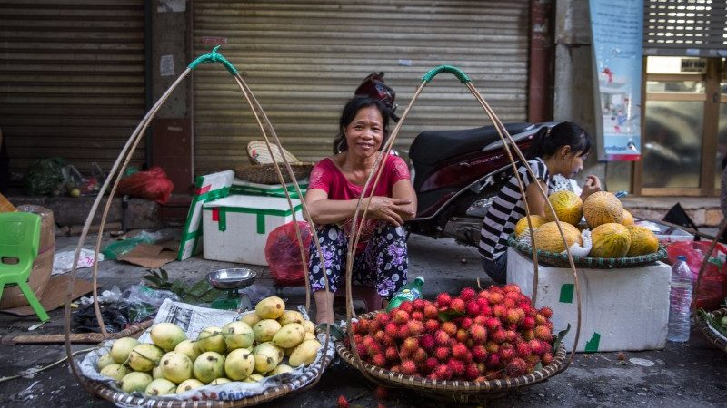 A street seller smiles at the camera on a busy Vietnam street