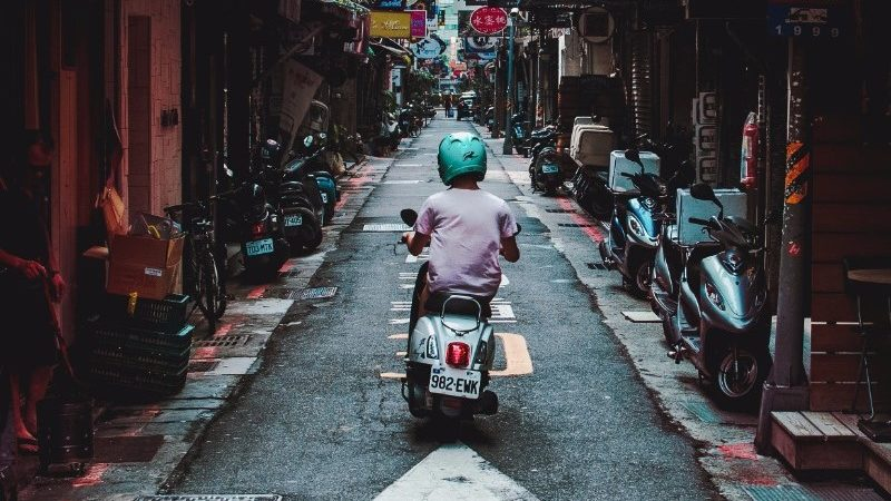 A man on a motorbike zips through the streets of Taipei