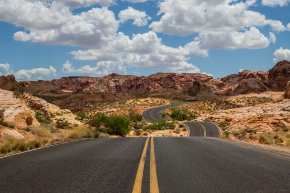 An open road stretches through the desert