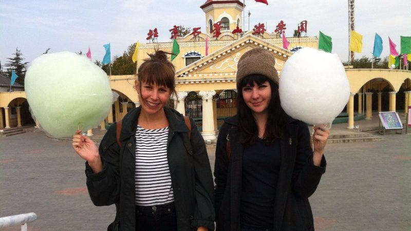 The writer and friend pose with two sticks of fairy floss.
